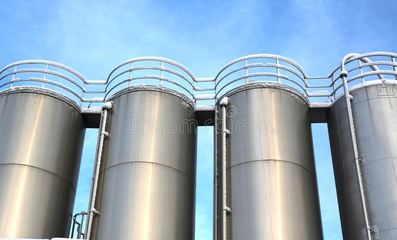 Stainless steel silos in the chemical industry. Bulk plastics silo against a blue sky royalty free stock image