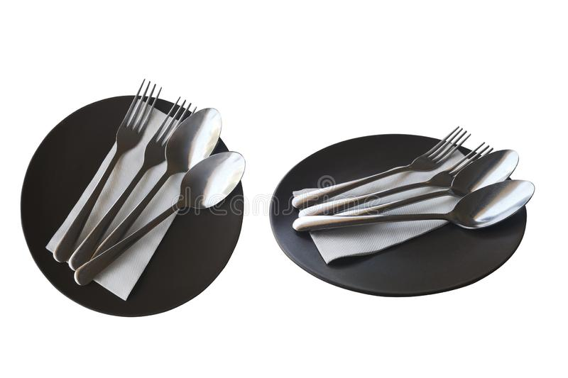 Stainless steel spoon and fork on a black ceramic plate,isolated on white background with clipping path.  royalty free stock photography