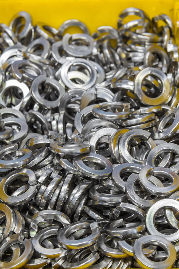 Stainless steel spring washers. Close up of stainless steel spring washers in yellow plastic tray in the factory, a shop floor item stock photography