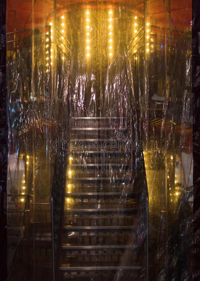 Stainless steel stairs up to the light behind a plastic cover stock photo