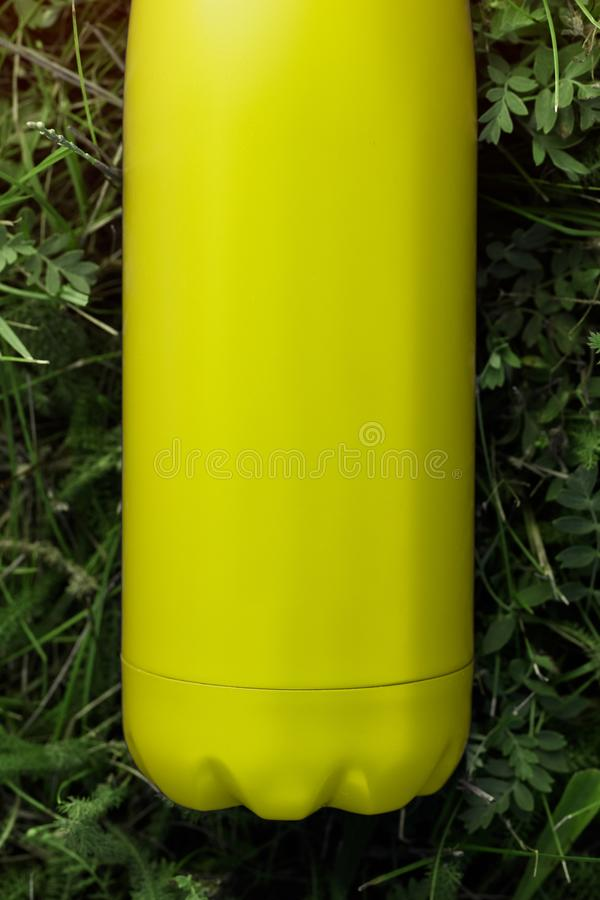 Stainless thermos water bottle, light lemon color. Light yellow. Mockup isolated on green grass background with sunlight effect. G. Lossy aluminum vacuum thermo stock photography