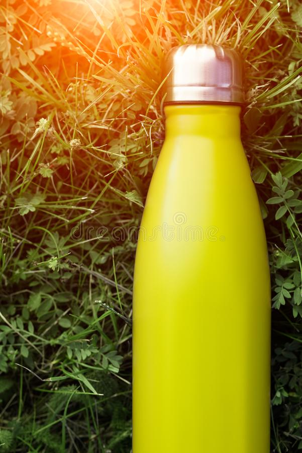 Stainless thermos water bottle, light lemon color. Light yellow. Mockup isolated on green grass background with sunlight effect. G. Lossy aluminum vacuum thermo stock images