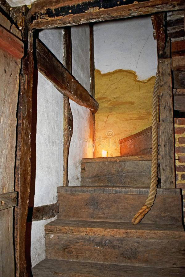 A stair case in a Tudor period house. A close up of a set of old wooden stairs and the stairway is lit by candle light as the house was in the Tudor period and stock photos