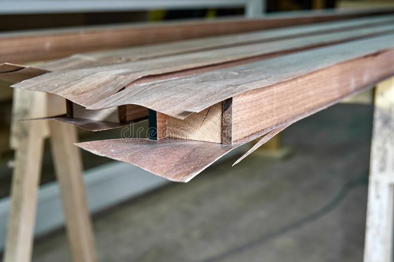 Stair handrail building process. Production of wood furniture. Furniture manufacture. Close-up. Solid walnut handrail with veneer in process of production in royalty free stock photography