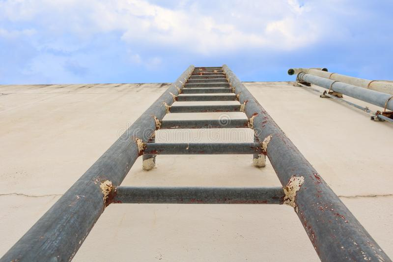 Stair old vertical industrial metal rusted to Water tank no safety rails on blue sky background royalty free stock photo