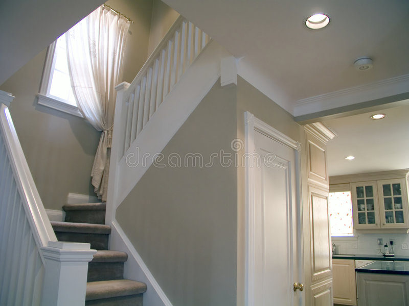 Staircase 10. Carpeted staircase with white wood railings, window, curtain and painting in an upscale house royalty free stock photos