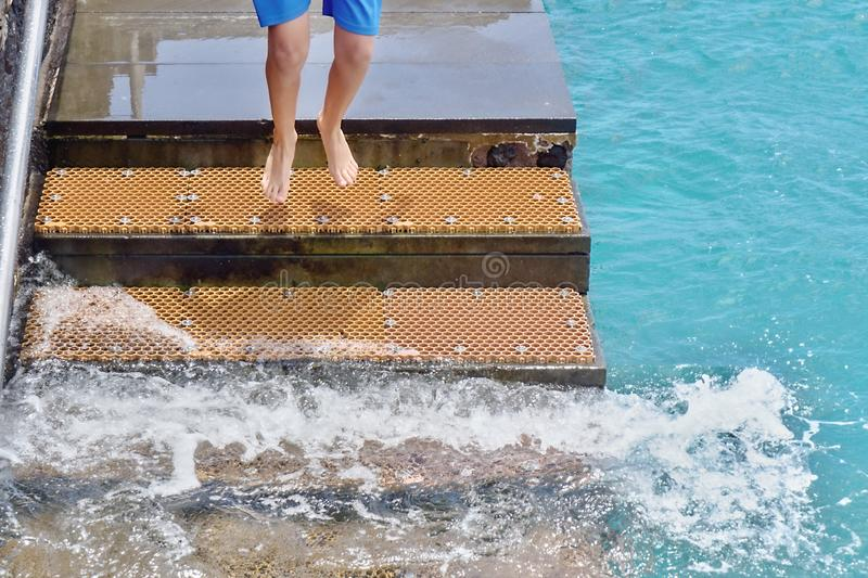 A staircase for bathers in the Atlantic Ocean, a young man jumping down. The stairs, he is currently in the air, face and torso are not visible royalty free stock images