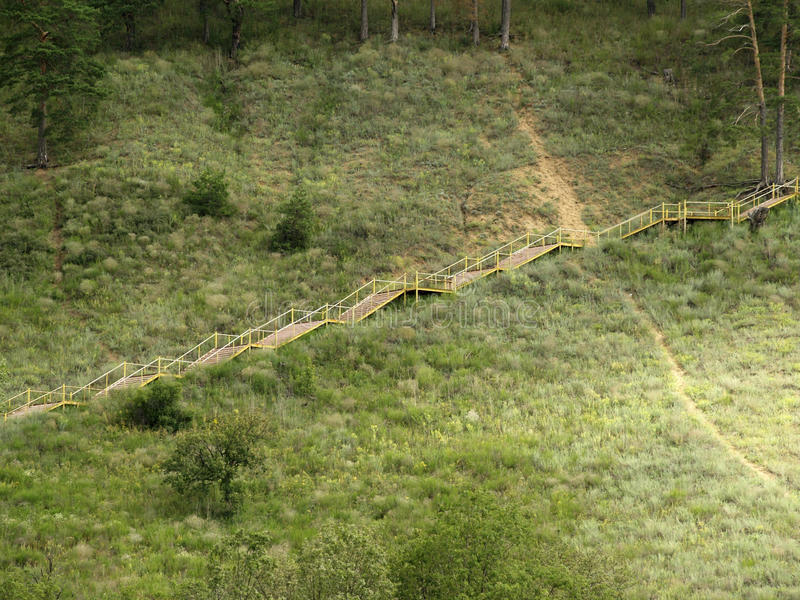 Staircase descends from the mountain. Visible path, Bush, pine . a staircase rises from left to right stock images