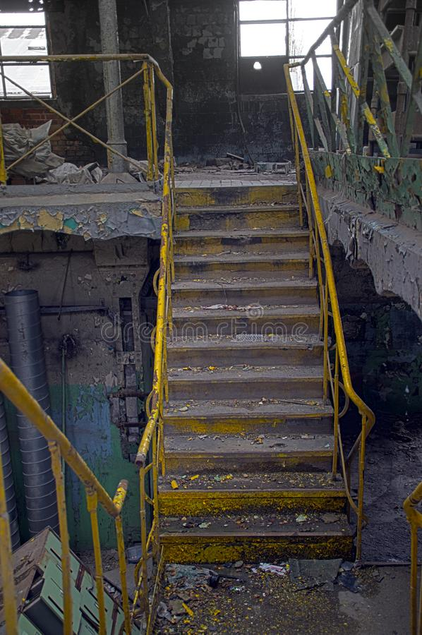 Staircase in factory. Stairway with yellow railing in a ruined industrial interior. Forgotten old factory stock photography
