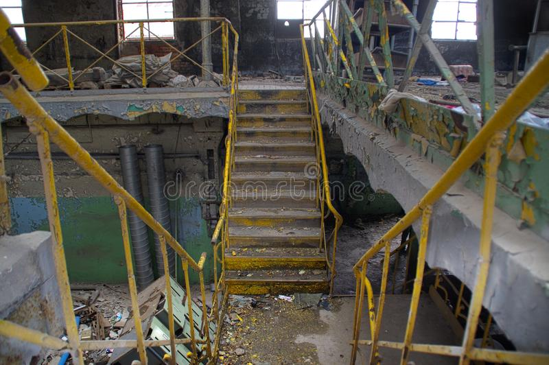 Staircase in factory. Stairway with yellow railing in a ruined industrial interior. Forgotten old factory stock image