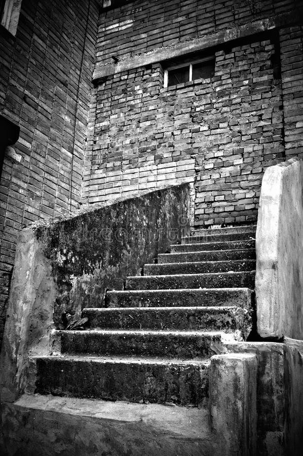 The staircase leading into brick wall. B&W stock photo