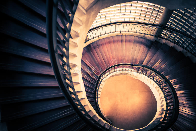 Staircase in spiral or swirl shape, fibonacci golden ratio composition, abstract or architecture concept, dark vintage mysterious stock image