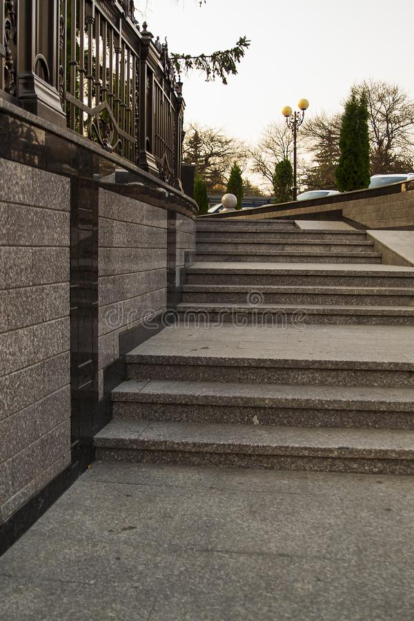 A staircase with stone steps and wrought-iron railings descends. The concept of the city stock photography