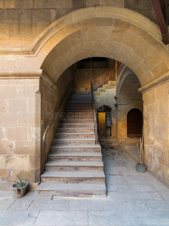Staircase with wooden balustrade leading to an old abandoned historic building, Cairo, Egypt. Exterior daylight shot of staircase going up leading to Caravansary stock photo
