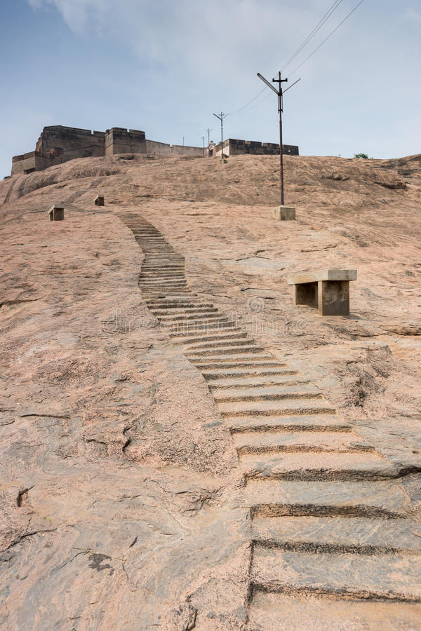 Stairs in boulder leading to Dindigul Rock Fort. Dindigul, India - October 23, 2013: Stairs hewed in huge boulder leading to historic Dindigul Rock Fort. Brown royalty free stock photo