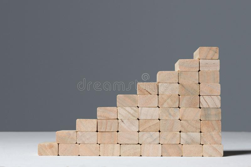 Stairs to success build with wooden blocks on grey background with copy space. Stairs build with wooden blocks on grey background stock photos