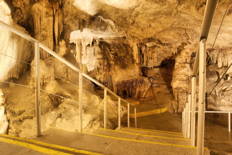 Stairs in a cave leading to a huge chamber royalty free stock photo