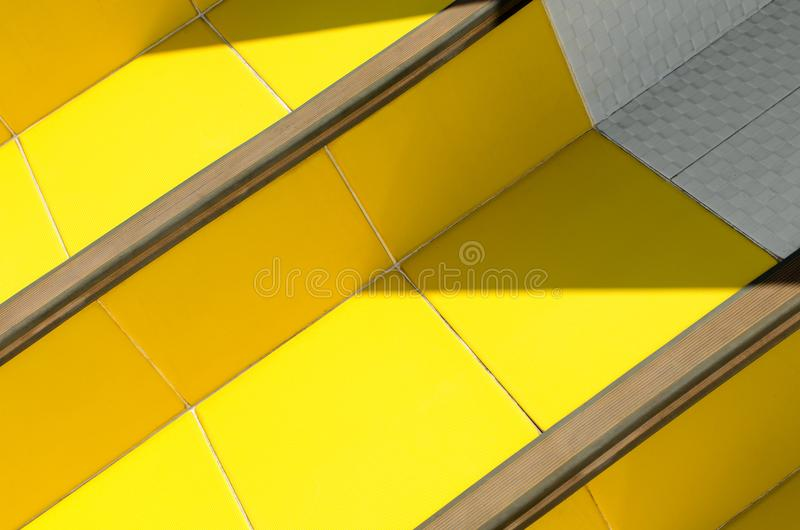 Stairs of ceramic tiles of warm yellow, illuminated by sun with darkened corners. Abstract bright background - stairs of ceramic tiles of warm yellow royalty free stock photo