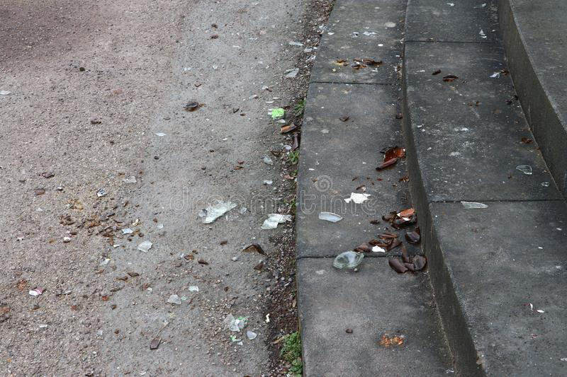 Stairs and ground full with broken glass and bottles stock image