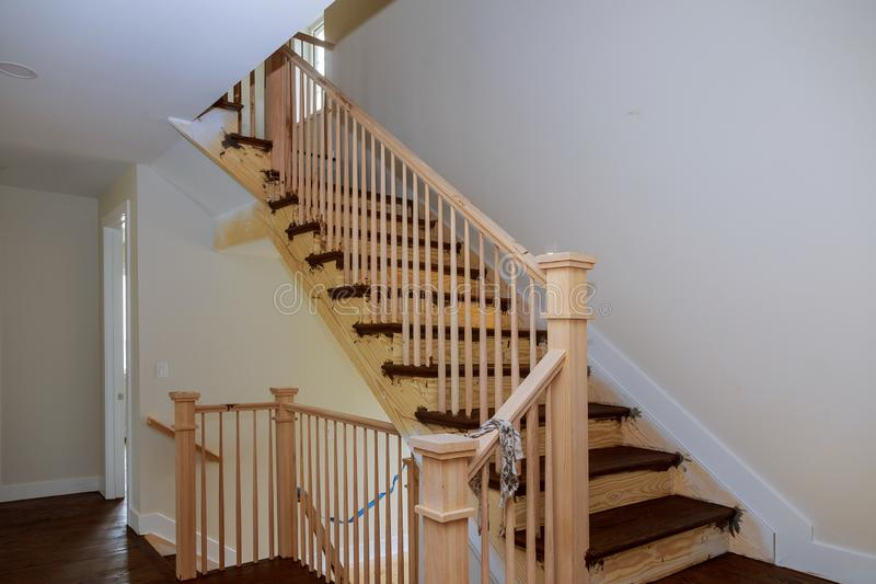 Stairs handrails renovation.wizard for wooden railing for stairs Wooden planks around pole. Stairs handrails renovation installation of wood stairs wizard for stock photos