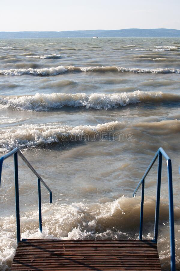 Stairs at lake Balaton in stormy weather with waves royalty free stock photo