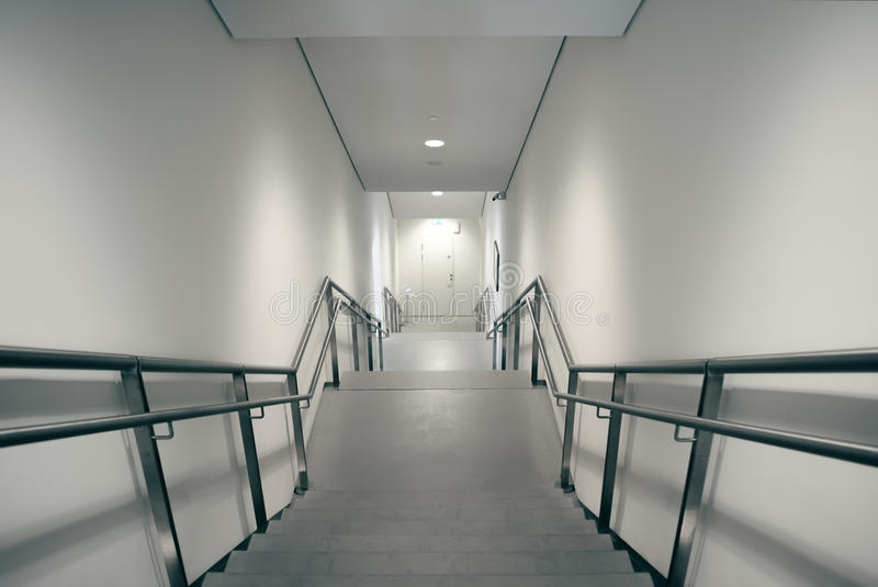 Stairs leading down to emergency exit. Stair with sharp angles leading down to an emergency escape door stock image