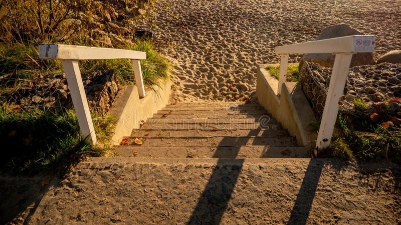 Stairs leading to an empty beach. Shadows and sunlights. Natural light royalty free stock photos