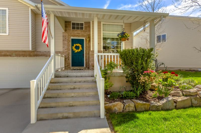 Stairs leading to the porch and front door of a home with a lovely garden. The facade is decorated with an American flag, yellow wreath, and hanging potted stock images