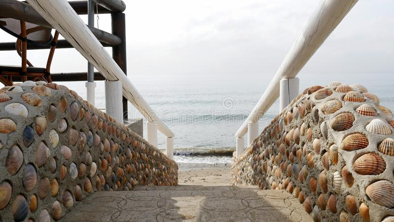 Stairs made of shells and wooden handrail leading to the sea. stock photos
