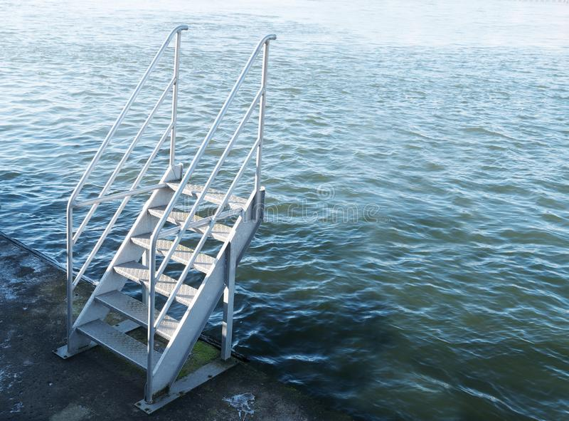 stairs of metal at the harbor leads upward to nothing, only water, copy space stock photography