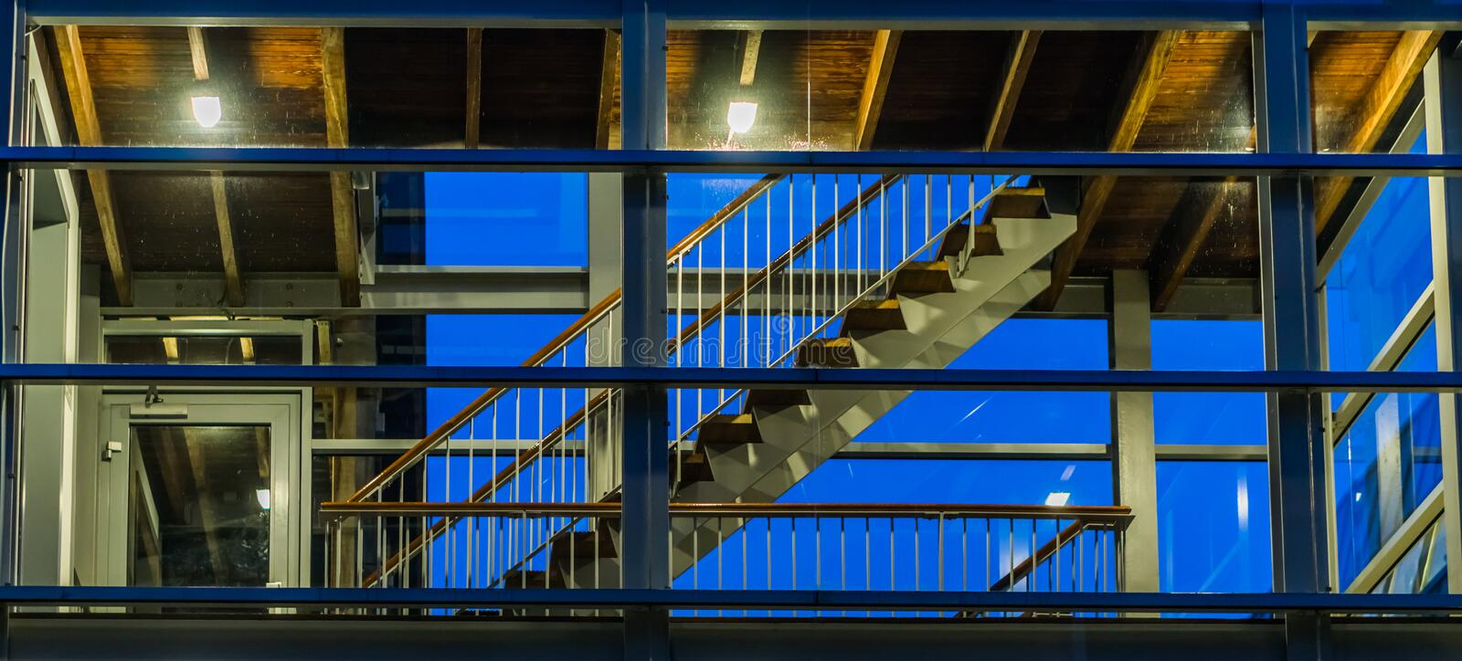 Stairs in a modern staircase building with glass windows, lighted at night, dutch architecture stock photo