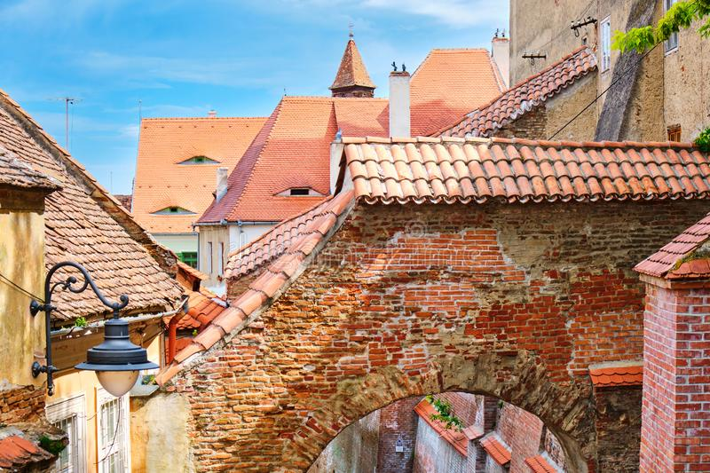 Stairs Passage in Sibiu, Romania. Top view of the arch and traditional houses with roofs and eye-like windows, on a bright day stock photo