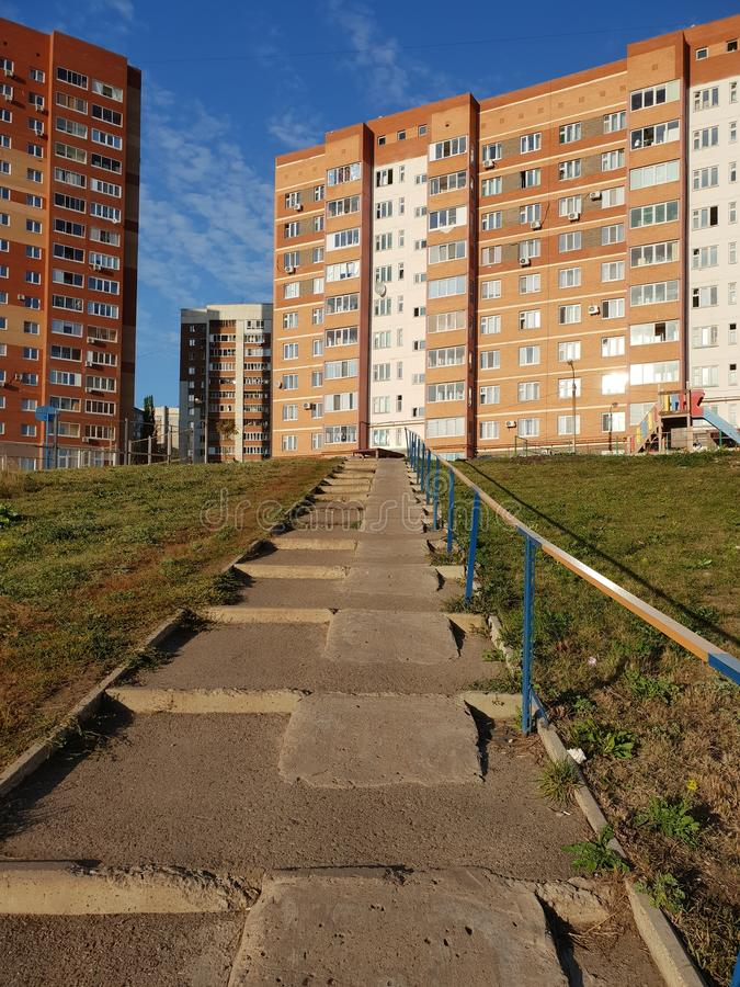 Stairs with ramps. Asphalt stairway with ramps goes up to the city, houses around, architecture of small towns, clear blue sky, city walk, park, path stock images