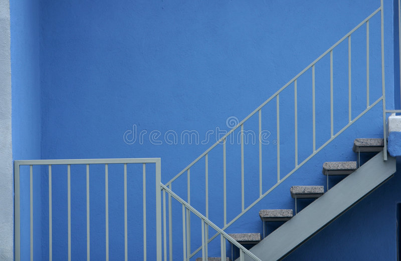 Stairs with Safety Railing against Blue Wall stock photos