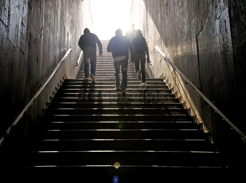 Stairs to light. People walking up the stairs to light stock photos