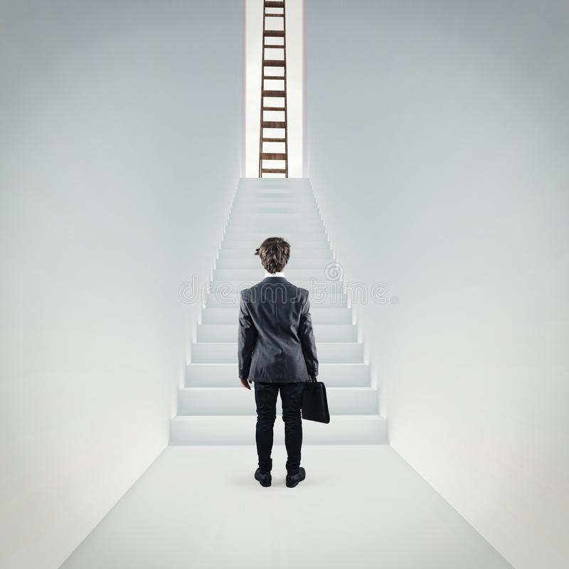 Stairs to success. Businessman standing in a hallway in front of the stairs . Ladder on top of the stairs. The concept of success royalty free stock images