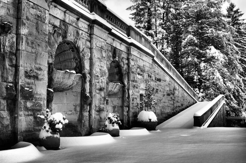Stairs to a Winter Wonderland. Winter snow fall covers stairs to Diana Goddess of the hunt in black and white stock photo