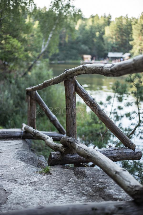 Stairs up from old wooden cracked logs. Railing at cliff in canyon stock image