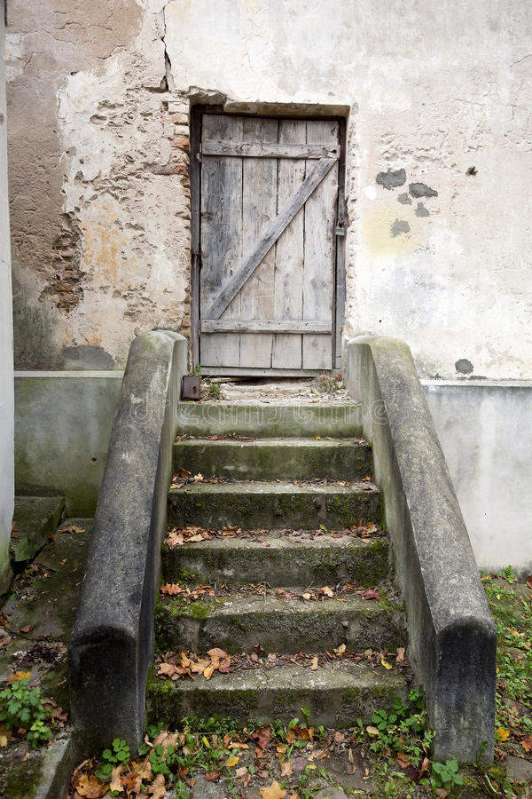 Stairs and wooden door in a wall. Stairs and wooden door in an old wall stock image