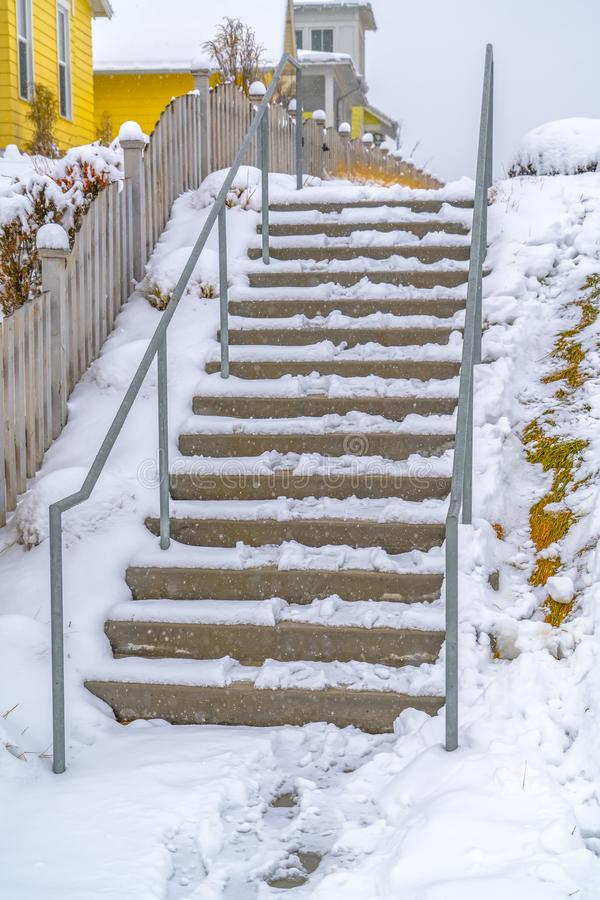 Stairs beside wooden fence of a home in winter. Outdoor stairs beside the wooden fence of a home in Daybreak, Utah. Snow covers the landscape and structure stock photos