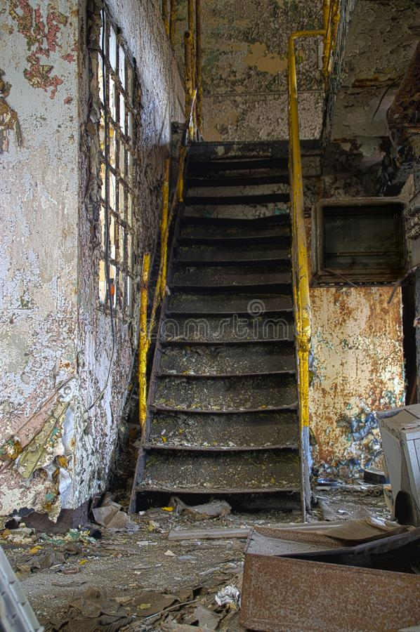 Staircase in factory. Stairs with yellow railing in a ruined industrial interior. Abandoned old factory royalty free stock image