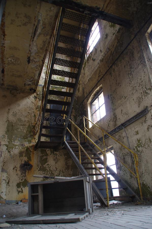Staircase in factory. Stairs with yellow railing in a ruined industrial interior. Abandoned old factory stock images