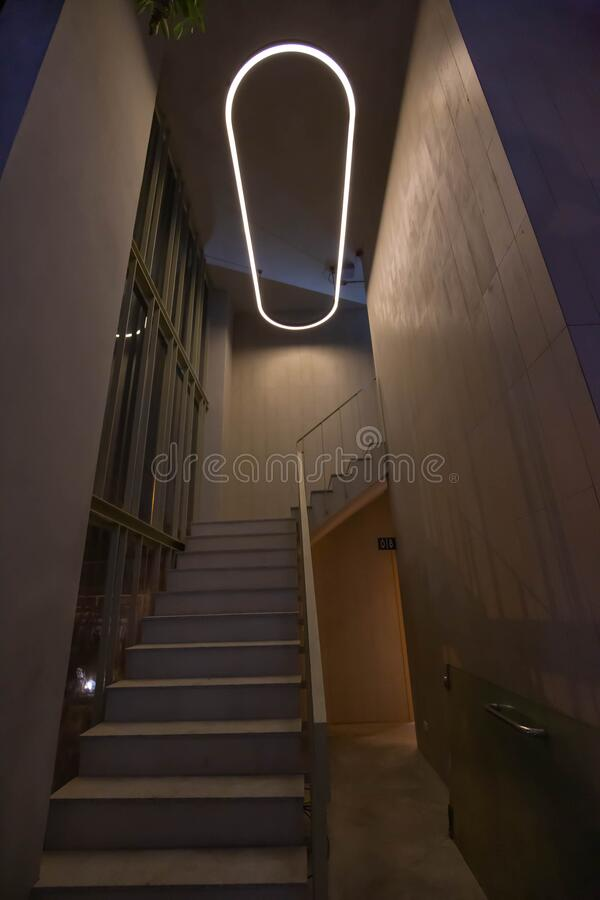 Stairway in modern building with lamp design hanging on the ceiling. concrete gray wall royalty free stock photography