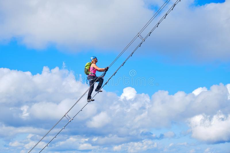 Stairway to heaven concept. Woman climbing a diagonal via ferrata ladder in Donnerkogel mountains, Austria, near Gosau. Stairway to heaven concept. Woman stock photo