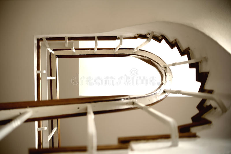 Stairway underview. The underview of a staircase with a spiral staircase and railings stock images