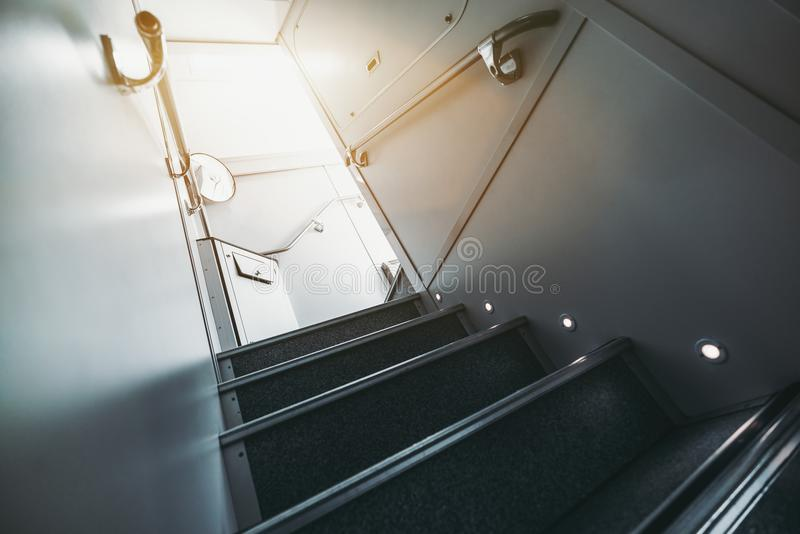 Stairway up of double-decker suburban train. Wide-angle view from bottom of modern staircase with floor illumination going up to second floor of two-storey stock image