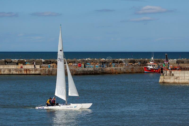 STAITHES, СЕВЕРНОЕ YORKSHIRE/UK - 21-ОЕ АВГУСТА: Большое белое плавание катамарана в гавань Staithes на 21,2010 -го августа стоковая фотография rf