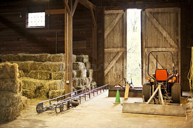 Stajni wnętrze z siana belami i rolnym wyposażeniem zdjęcia stock