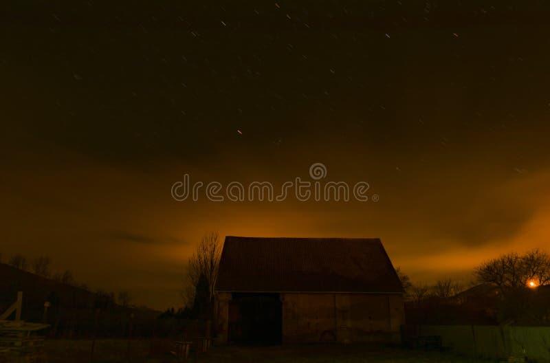 Stajnia z gwiazdowym niebem w zimy zimna nocy obraz stock