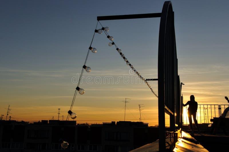 Staket och ljusa kulor och solnedgång arkivbild